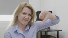 Zdegustowany młody bizneswoman pokazuje kciuki zestrzela znaka niechęć - zdjęcie wideo