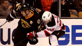 Zdeno Chara v. Patrik Elias (NHL Hockey). Boston Bruins defenseman Zdeno Chara (33) tries to shake off New Jersey Devils forward Patrik Elias (26 Stock Photography