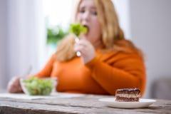 Zdewastowana tłuściuchna kobieta patrzeje ciastka fotografia royalty free