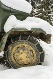 Snow chains mounted on the wheel of a truck. Stock Photo