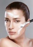 Zdrój dziewczyna z śmietanką na Jej twarzy. Skincare pojęcie Fotografia Stock