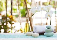 Zdrój i wellness masaż ustawia Wciąż życie z świeczki, ręcznika i kamieni lata Plenerowym tłem, Zdjęcie Royalty Free