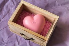 Zdrój i wellness pojęcie: drewniany pudełko z różową morze solą i kierowy kształta mydło z słowa ` kochamy ` na nim Obrazy Stock
