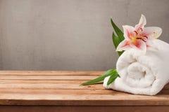Zdrój i wellness pojęcie z białym kwiatem na drewnianym stole nad wieśniaka popielatym tłem i ręcznikiem zdjęcie stock