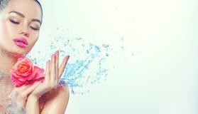 Zdrój Kobieta Piękno uśmiechnięta dziewczyna z pluśnięciami woda i wzrastał w jej rękach Obrazy Royalty Free