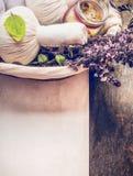Zdrój lub wellness tło z zakończeniem up ziołowi masażu kompresu piłek, ręcznika, solankowych i świeżych ziele w koszu na drewnia Zdjęcie Stock