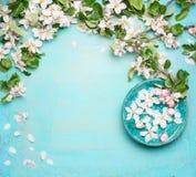 Zdrój lub wellness turkusowy tło z okwitnięciem i wodą rzucamy kulą z białymi kwiatami, odgórny widok zdjęcia stock