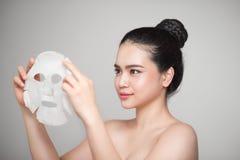 Zdrój, opieka zdrowotna Azjatycka dziewczyna z kosmetyczną maską Obrazy Royalty Free