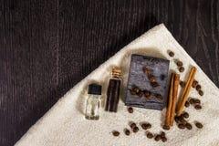 Zdrój ustawiający w brązie: naturalny mydło, aromatyczny olej, cynamonowi kije, kawowe fasole i ręcznik na drewnianym tle, obraz stock