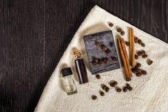 Zdrój ustawiający w brązie: naturalny mydło, aromatyczny olej, cynamonowi kije, kawowe fasole i ręcznik na drewnianym tle, zdjęcia stock