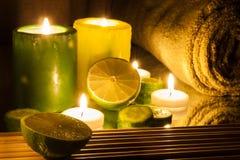 Zdrój, wellness położenie zielony i żółte świeczki zaświecać, cytryny zieleń Zdjęcia Stock