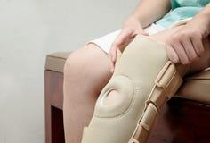 Zdradzona kobieta jest ubranym elastycznego kolanowego bras w rehabilitaci cente obrazy stock