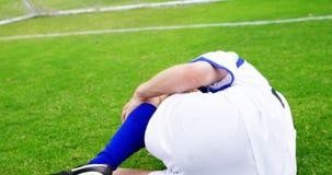 Zdradzony gracza futbolu lying on the beach na trawie zbiory