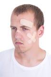 Zdradzony mężczyzna z adhezyjnym tynkiem na jego twarzy Zdjęcie Royalty Free