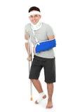 Zdradzony młody człowiek odzieży ręki temblak i szczudło fotografia stock