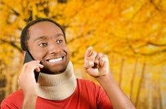 Zdradzony młody pozytywny czarny latynoski męski jest ubranym szyja bras i opowiadać na telefonie ono uśmiecha się, żółty abstrak Obrazy Royalty Free