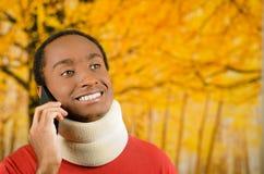 Zdradzony młody pozytywny czarny latynoski męski jest ubranym szyja bras i opowiadać na telefonie ono uśmiecha się, żółty abstrak Fotografia Royalty Free