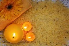 Zdrojów produktów żółty ustawiać Morza sól, ręcznik i świeczki na ciemnym drewnianym tle, Obraz Stock