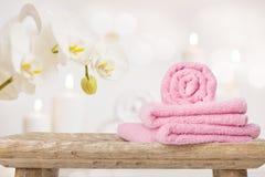 Zdrojów ręczniki na drewnianym stole i orchidei nad abstrakcjonistycznym tłem Zdjęcie Stock