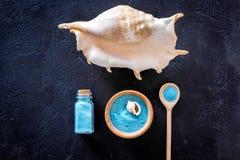 Zdroju kosmetyczny ustawiający z morze solą dla skąpania i skorupy na zmroku - błękitny tło odgórnego widoku mockup Zdjęcie Stock