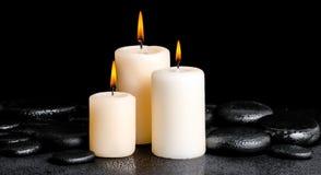 Zdroju pojęcie białe świeczki na zen bazalta kamieniach z kroplami zdjęcia stock
