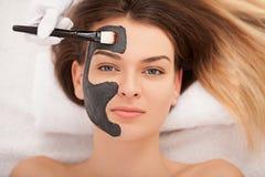 Zdroju pojęcie Młoda kobieta z odżywki twarzową maską w piękna sal zdjęcia royalty free