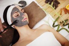 Zdroju pojęcie Młoda kobieta z odżywki twarzową maską w piękna sal obrazy stock