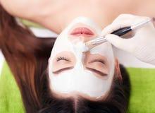 Zdroju pojęcie Młoda kobieta z odżywki twarzową maską w piękno salonie, zamyka up zdjęcia royalty free