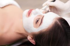 Zdroju pojęcie Młoda kobieta z odżywki twarzową maską w piękno salonie, zamyka up obrazy stock