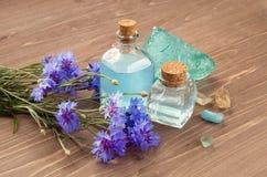 ZDROJU salon, aromatherapy lub kosmetyka pojęcie, Błękitna chabrowa kwiat woda w szklanych butelkach i kąpielowej soli na drewnia obrazy stock