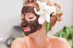 Zdroju salon Piękna kobieta z twarzową maską przy piękno salonem zdjęcia stock