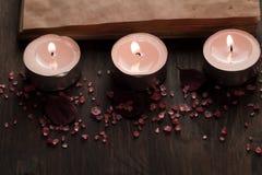 Zdroju skład z aromat świeczkami i pustego rocznika otwartą książką na drewnianym tle Traktowanie, aromatherapy Zdjęcia Stock