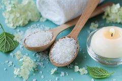 Zdroju skład z morze solą w drewnianej łyżce, kąpielowym ręczniku, białych kwiatach i płonących świeczkach na błękitnej drewniane Zdjęcie Royalty Free
