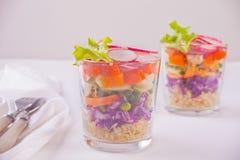 Zdrowa świeża sałatka w glassful z czerwoną kapustą, pomidorem, quinoa, zieloną sałatką i rzodkwią na białym stole, zdjęcie royalty free