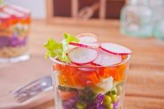 Zdrowa świeża sałatka w glassful z czerwoną kapustą, pomidorem, quinoa, zieloną sałatką i rzodkwią na drewnianym stole, obrazy stock