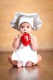zdrowa żywność Zdziwiony mały szef kuchni z czerwonym pieprzem w ręce Obraz Royalty Free