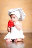 zdrowa żywność Zdziwiony mały szef kuchni z czerwonym pieprzem w ręce Obrazy Royalty Free