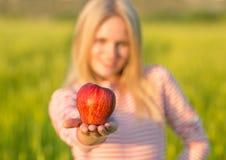 Zdrowa atrakcyjna kobieta eatiing czerwonego jabłka zielone pola lato fotografia stock