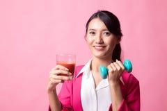Zdrowa Azjatycka kobieta z dumbbell i pomidorowym sokiem obrazy stock