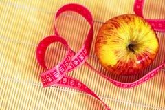 Zdrowa dieta: jabłczana i pomiarowa taśma Obrazy Royalty Free