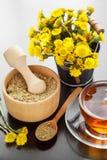 Zdrowa herbata, wiadro dalej z coltsfoot kwiatami i drewniany moździerz, Obrazy Royalty Free
