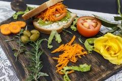Zdrowa jarska kanapka z marchewką, pomidor sałata i pikantność, słuzyć na drewnianej desce z kolor żółty różą, zdjęcie stock