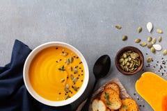 Zdrowa jesieni bani kremowa polewka w pucharze słuzyć z ziarnami i crouton na kamiennym stołowym odgórnym widoku zdjęcie stock