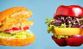 Zdrowa kanapka z świeżym pieprzem, cebulą, sałatkową sałatą i niezdrowym szkodliwym hamburgerem, Obraz Stock
