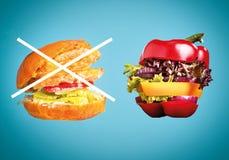 Zdrowa kanapka z świeżym pieprzem, cebulą, sałatkową sałatą i niezdrowym szkodliwym hamburgerem, Obrazy Stock