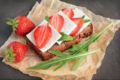 Zdrowa kanapka z żyto chlebem, świeżą truskawką, arugula i miękkim serem na pergaminie, Obraz Royalty Free