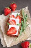 Zdrowa kanapka z żyto chlebem, świeżą truskawką, arugula i miękkim serem na pergaminie, Obrazy Stock