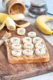 Zdrowa kanapka z masłem orzechowym, bananem i chia crunchy, sia, na drewnianej desce, składniki na tle, pionowo Zdjęcie Royalty Free