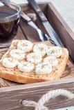 Zdrowa kanapka z masłem orzechowym, bananem i chia crunchy, sia, w drewnianej tacy z filiżanką kawy, pionowo Obrazy Stock