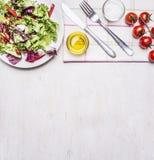 Zdrowa karmowa świeża sałatka na białym talerzu z olejem, sól, nóż i rozwidlenie pieluchy granica na drewnianym wieśniaku, miejsc Zdjęcia Royalty Free